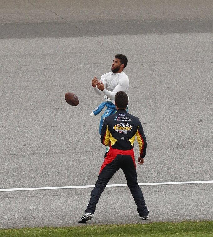Bubba Wallace catches a football from the fans as Corey LaJoie looks on during a rain delay at the NASCAR cup series auto race at Michigan International Speedway, Sunday, June 9, 2019, in Brooklyn, Mich. The race has been rescheduled for Monday. (AP Photo/Carlos Osorio)