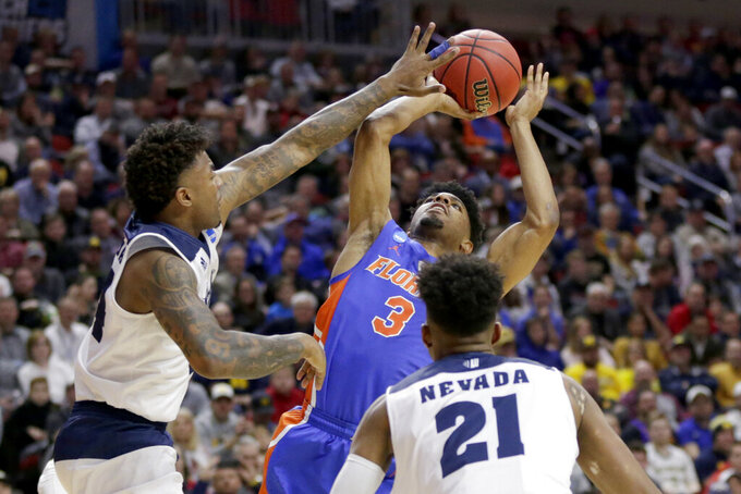 Florida's Jalen Hudson (3) tries to shoot past the defense of Nevada's Jordan Caroline, left, during the second half of a first round men's college basketball game in the NCAA Tournament, in Des Moines, Iowa, Thursday, March 21, 2019. (AP Photo/Nati Harnik)