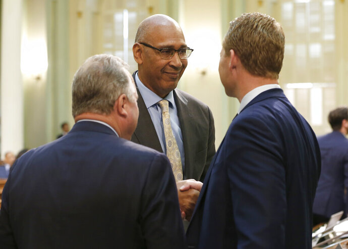 Assemblyman Chris Holden, D-Pasadena, center, shakes hands with Assemblyman Chad Mayes, R-Yucca Valley, after their wildfire measure they co-authored, along with Assemblywoman Autumn Burke, D-Inglewood was approved by the Assembly in Sacramento, Calif., Thursday, July 11, 2019. The bill, AB1054, aimed at stabilizing the state's electric utilities in the face of devastating wildfires caused by their equipment, was approved overwhelmingly and now goes to the governor. At left is state Sen. Bill Dodd, D-Napa, who carried the measure in the Senate. (AP Photo/Rich Pedroncelli)