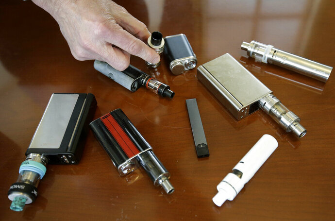 In this Tuesday, April 10, 2018 photo, Marshfield High School Principal Robert Keuther displays vaping devices that were confiscated from students in such places as restrooms or hallways at the school in Marshfield, Mass. Illinois health officials are reporting what could be United States' first death tied to vaping. In a Friday, Aug. 23, 2019, news release, the Illinois Department of Public Health says a person who recently vaped died after being hospitalized with