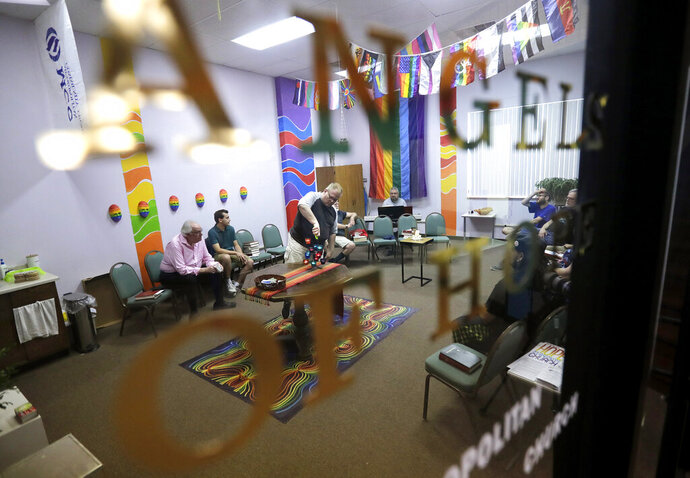 Ken Sann lights candles while members of Angels of Hope Metropolitan Community Church speak prayers of joy and concern during a worship service Sunday, Aug. 18, 2019 in Kaukauna, Wis. (Danny Damiani/The Post-Crescent via AP)/The Post-Crescent via AP