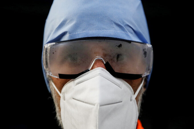 Medical staffer Paolo Pozzoli looks into the camera with cloudy goggles during his shift at the Biassono White Cross ambulance emergency headquarter, Monza, Italy, Thursday, Nov. 19, 2020. The city of Monza north of Milan is best known for its Formula 1 racetrack. In 2020, it has been the ambulance service that has been doing most of the racing. Over three days that an Associated Press photographer traveled on night calls with an ambulance service, the Monza-Brianza province of some 875,000 bordering Milan added 2,500 new cases, part of Italy's new epicenter in the Lombardy region. (AP Photo/Luca Bruno)