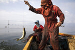 Fishermen wearing oil stained uniforms from Venezuela's state-run oil firm PDVSA, catch bass known as