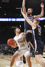Georgia Tech guard Jose Alvarado looks to pass off on a double-team by Virginia defenders Jay Huff, top, and Sam Hauser during an NCAA college basketball game Wednesday, Feb. 10, 2021, in Atlanta. (Curtis Compton/Atlanta Journal-Constitution via AP)