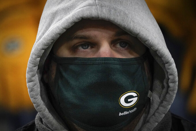 A masked spectator watches during the second half of an NFL divisional playoff football game between the Green Bay Packers and the Los Angeles Rams Saturday, Jan. 16, 2021, in Green Bay, Wis. (AP Photo/Morry Gash)
