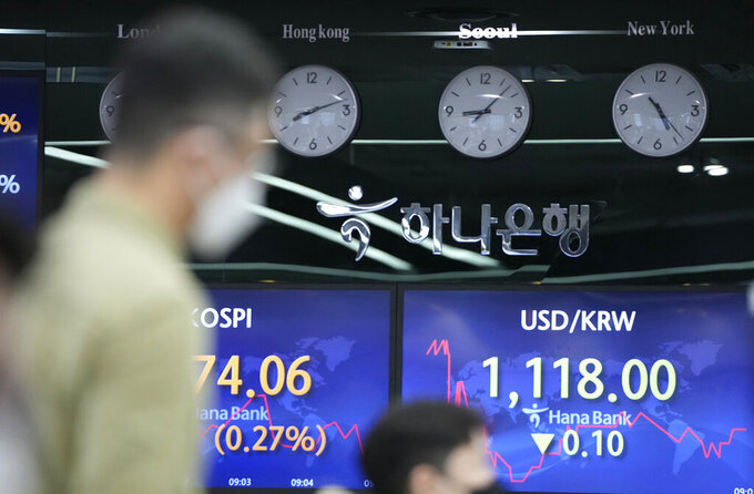 Currency traders watch computer monitors near the screens showing the Korea Composite Stock Price Index (KOSPI), left, and the foreign exchange rate between U.S. dollar and South Korean won at the foreign exchange dealing room in Seoul, South Korea, Friday, May 28, 2021. Asian shares rose Friday, powered by encouraging signs that the U.S. economic recovery from the pandemic is gaining momentum. (AP Photo/Lee Jin-man)