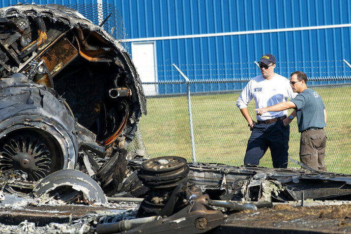 Members of the National Transportation Safety Board looks at the wreckage of a plane that Dale Earnhardt Jr., his wife and daughter and two pilots and a dog were on when it crash landed Thursday at the Elizabethton Municipal Airport in Elizabethton, Tenn., Friday, Aug. 16, 2019. Earnhardt Jr. will take the weekend off from broadcasting to be with his wife and daughter after the crash near Bristol Motor Speedway. (David Crigger/Bristol Herald Courier via AP)