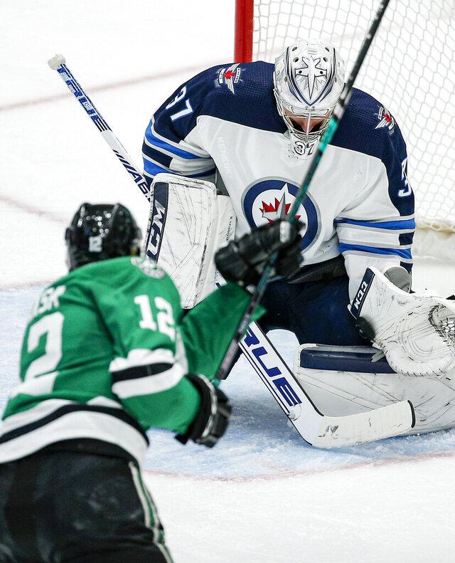 Winnipeg Jets goaltender Connor Hellebuyck (37) stops a shot from Dallas Stars forward Radek Faksa (12) during the second period of an NHL hockey game Thursday, Dec. 5, 2019, in Dallas. (AP Photo/Brandon Wade)