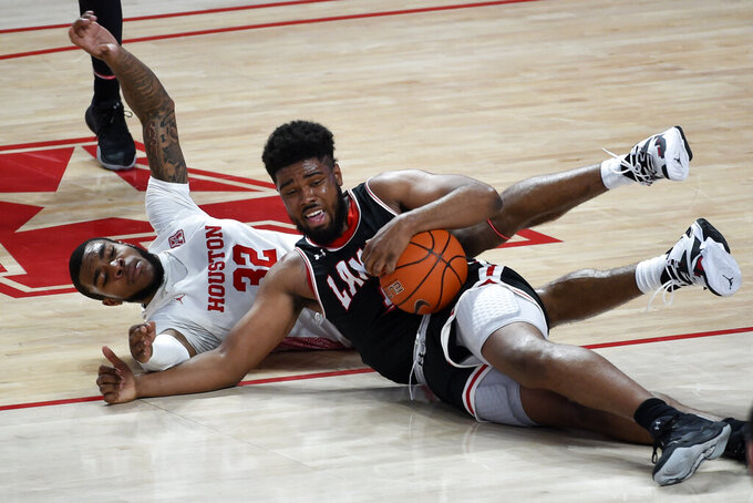 Lamar forward Avery Sullivan, right, grabs a loose ball from Houston forward Reggie Chaney during the first half of an NCAA college basketball game, Wednesday, Nov. 25, 2020, in Houston. (AP Photo/Eric Christian Smith)