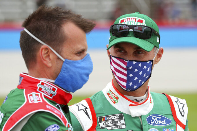 Crew chief Rodney Childers talks with driver Kevin Harvick (4) as they wait on the grid before a NASCAR Cup Series auto race at Texas Motor Speedway in Fort Worth, Texas, Sunday, Oct. 25, 2020. (AP Photo/Richard W. Rodriguez)