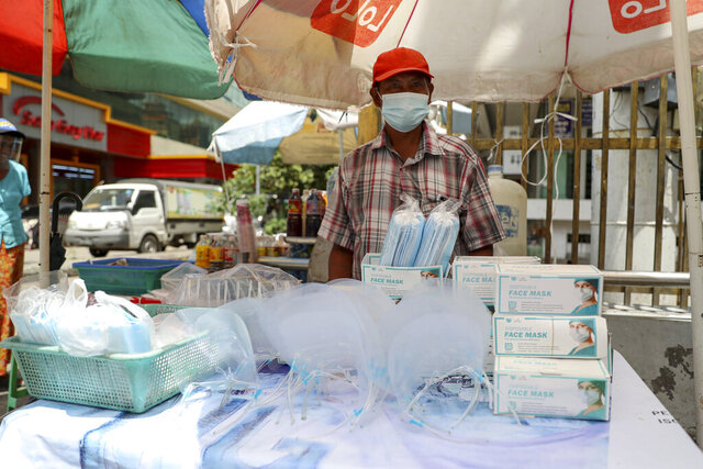 A vendor selling face masks and shields waits for customers at a roadside shop in Yangon, Myanmar, Thursday, Sept. 10, 2020. Myanmar is accelerating efforts to control the spread of the coronavirus, which now has impinged on the upcoming November 8 general election, as campaigning has been ordered suspended in several areas locked down to control the spread of the virus. (AP Photo/Thein Zaw)