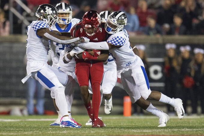 Louisville wide receiver Jaylen Smith (9) is tackled by several Kentucky defenders during the second half of an NCAA college football game in Louisville, Ky., Saturday, Nov. 24, 2018. (AP Photo/Bryan Woolston)