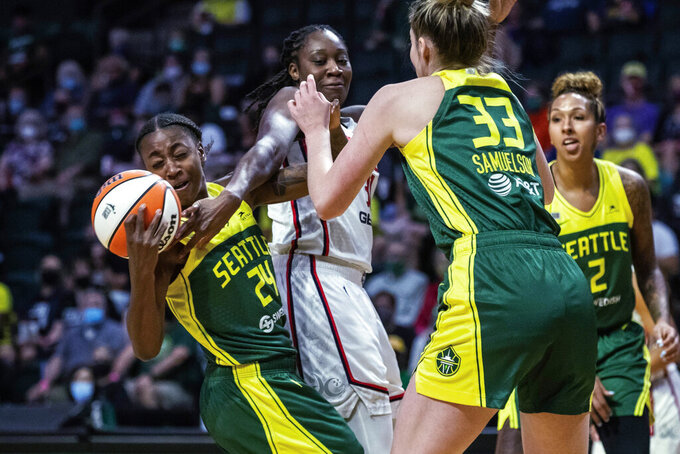 Seattle Storm's Jewell Loyd, left, strips the ball from Washington Mystics' Tina Charles in the lane, but can't retain possession during the first quarter of a WNBA basketball game Tuesday, Sept. 7, 2021, in Everett, Wash. (Dean Rutz/The Seattle Times via AP)