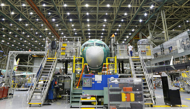 FILE - In this Dec. 7, 2015 file photo, a Boeing 737 MAX airplane being built is shown on the assembly line in Renton, Wash. Orders to U.S. factories for big-ticket manufactured goods rose in December 2019 as a big jump in demand for military aircraft offset a sharp decline in commercial aircraft.  Demand for commercial aircraft fell a sharp 74.7 percent, reflecting the struggle Boeing has had getting its troubles Boeing has had with its troubled 737 Max plane following two fatal crashes. (AP Photo/Ted S. Warren)