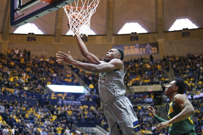 West Virginia forward Oscar Tshiebwe (34) shoots ahead of Baylor guard Devonte Bandoo (2) during the second half of an NCAA college basketball game Saturday, March 7, 2020, in Morgantown, W.Va. (AP Photo/Kathleen Batten)