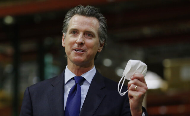 Gov. Gavin Newsom displays a face mask as he urges people to wear them to fight the spread of the coronavirus during a news conference in Rancho Cordova, Calif., Friday, June 26, 2020. Newsom said he wants Imperial County in Southern California to reimpose a stay-at-home order amid a surge in positive coronavirus tests. (AP Photo/Rich Pedroncelli, Pool)