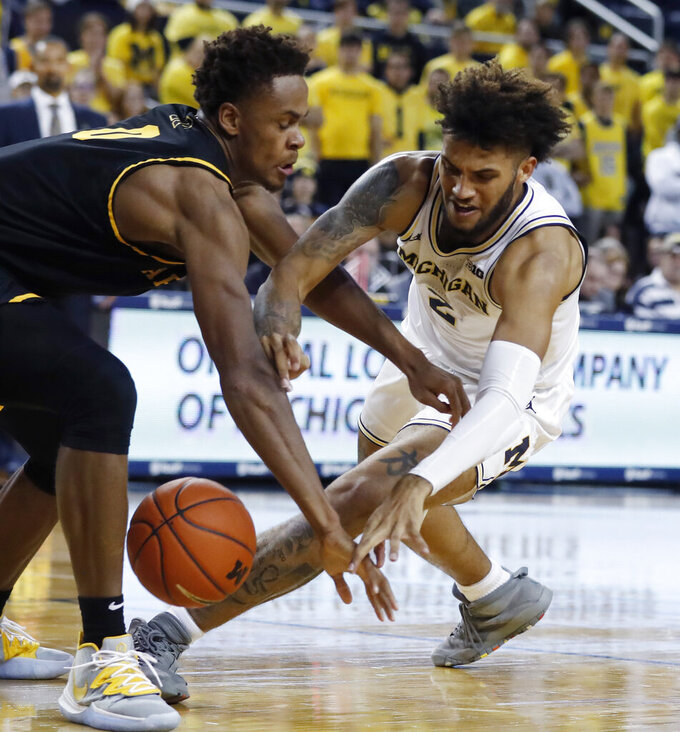 Appalachian State forward Isaac Johnson (0) and Michigan forward Isaiah Livers (2) reach for the loose ball during the second half of an NCAA college basketball game, Tuesday, Nov. 5, 2019, in Ann Arbor, Mich. (AP Photo/Carlos Osorio)