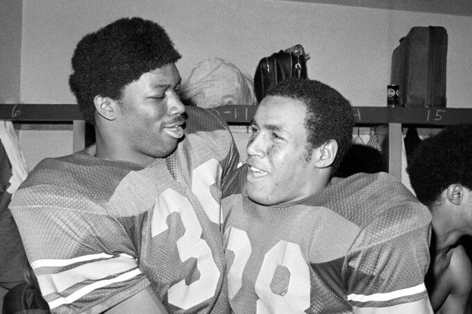 FILE - In this Jan. 1, 1973, file photo, Southern California fullback Sam Cunningham, left, and running back Anthony Davis embraces in locker room after USC.s 42-17 triumph in the Rose Bowl NCAA college football game against Ohio State in Pasadena, Calif. Cunningham, an All-American fullback at Southern California whose performance against Alabama was credited for helping integrate football in the Deep South before he went on to a record-setting career with the New England Patriots, died Tuesday, Sept. 7, 2021, at his home in Inglewood, Calif., according to USC. He was 71. (AP Photo/File)