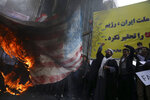 Iranian demonstrators chant slogans as they set fire a representation a makeshift U.S. flag during an annual rally in front of the former U.S. Embassy in Tehran, Iran, Monday, Nov. 4, 2019. Reviving decades-old cries of