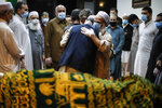 Mohammad Ayaz, cousin of Mohammad Altaf, center right, is hugged by a mourner after funeral prayers are given over Altaf's body at Al-Rayaan Muslim Funeral Services, Sunday, May 17, 2020, in the Brooklyn borough of New York. (AP Photo/John Minchillo)