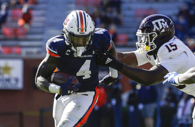 Auburn running back Tank Bigsby (4) gets around Texas A&M defensive lineman Jeremiah Martin (15) as he carries the ball during the second half of an NCAA college football game on Saturday, Dec. 5, 2020, in Auburn, Ala. (AP Photo/Butch Dill)