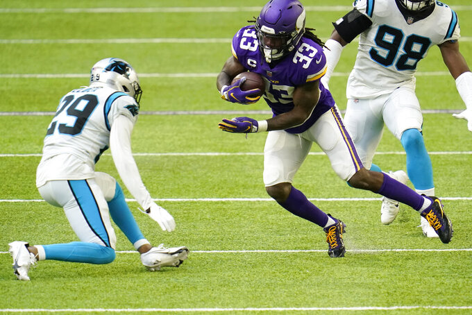 Minnesota Vikings running back Dalvin Cook (33) runs from Carolina Panthers cornerback Corn Elder (29) during the first half of an NFL football game, Sunday, Nov. 29, 2020, in Minneapolis. (AP Photo/Jim Mone)