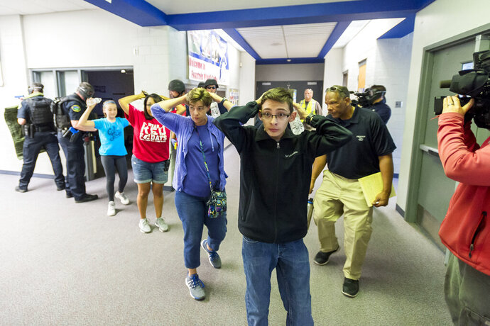FILE - In this Friday June 9, 2017 file photo, students are led out of school as members of the Fountain Police Department take part in an Active Shooter Response Training exercise at Fountain Middle School in Fountain, Colo. The nation's two largest teachers unions want schools to revise or eliminate active shooter drills, asserting Tuesday, Feb. 11, 2020 that they can harm students' mental health and that there are better ways to prepare for the possibility of a school shooting. (Dougal Brownlie/The Gazette via AP, File)
