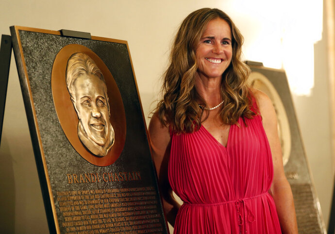 In this photo taken Monday May 21, 2018, Bay Area Sports Hall of Hame inductee Brandi Chastain poses by her plaque during a press conference in San Francisco. Social media is finding little to like about the likeness on a plaque honoring retired soccer champion Chastain. The Bay Area Sports Hall of Fame in San Francisco unveiled the plaque on Monday night. Chastain diplomatically said