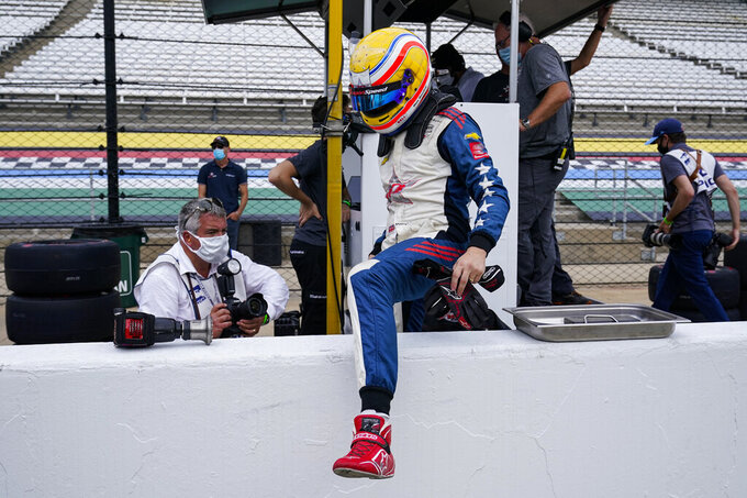 Ben Hanley, of England, climbs over the pit wall during practice for the Indianapolis 500 auto race at Indianapolis Motor Speedway in Indianapolis, Thursday, Aug. 13, 2020. (AP Photo/Michael Conroy)