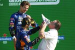 Zak Brown, right, drinks champagne from a shoe flanked by Mclaren drivers Daniel Ricciardo of Australia and Britain's Lando Norris, top, following the Formula One Grand Prix, at the Monza racetrack, Italy, Sunday, Sept. 12, 2021. Zak Brown returned to his home state at the top of the motor sports world following the 1-2 finish by McLaren at the Italian Grand Prix. It was the defining moment of a career that began as the wannabe racer from California climbed the motorsports ladder to CEO of McLaren Racing. Just seven days later, Brown was at Laguna Seca to watch McLaren's IndyCar team battle for the championship. (AP Photo/Luca Bruno)