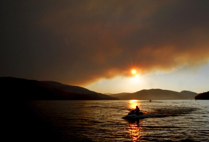 FILE - In this Aug. 6, 2007, file photo the sun begins to dip below wildfire smoke over Whitefish Lake in Whitefish, Mont. Whitefish city leaders are pursuing ways to make the community more sustainable amid wildfires, heat waves and drought as climate change intensifies. (Lido Vizzutti/Flathead Beacon via AP, File)