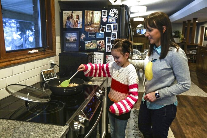 CORRECTS TO MISSY MILLARD-Missy Millard, left, cooks with her mom, Kim, in their home in Layton on Thursday, Jan. 28, 2021. (Annie Barker/The Deseret News via AP)