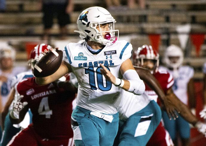 Coastal Carolina quarterback Grayson McCall (10) looks to pass during the first half of an NCAA football game against Louisiana-Lafayette in Lafayette, La., Wednesday, Oct. 14, 2020. (AP Photo/Paul Kieu)