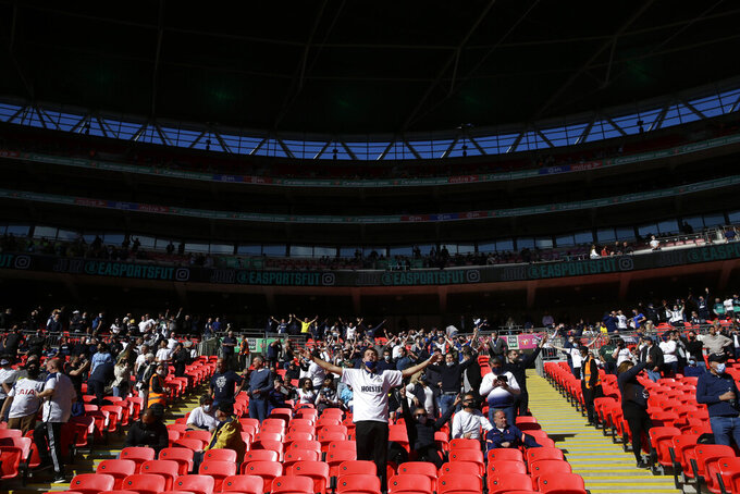 Tottenham supporters take their socially distanced seats for the English League Cup final soccer match between Manchester City and Tottenham Hotspur at Wembley stadium in London, Sunday, April 25, 2021. Some eight thousand spectators were allowed to attend the match. (AP Photo/Alastair Grant)