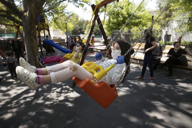 Children wearing face masks for protection against the coronavirus, play on swings in Kugulu public garden, in Ankara, Turkey, Wednesday, May 13, 2020. Parks filled with the sound of children as Turkey allowed those aged 14 and under to leave homes for the first time in 40 days. The country's youngest population were allowed to venture out for four hours between 11:00 am and 3:00 pm on Wednesday as Turkey eased some restrictions in place to fight to coronavirus outbreak.(AP Photo/Burhan Ozbilici)