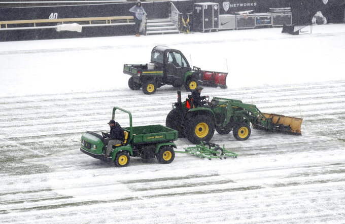 Grounds crew workers clear snow from the playing surface of Folsom Field before the first half of an NCAA college football game between Utah and Colorado Saturday, Nov. 17, 2018, in Boulder, Colo. (AP Photo/David Zalubowski)