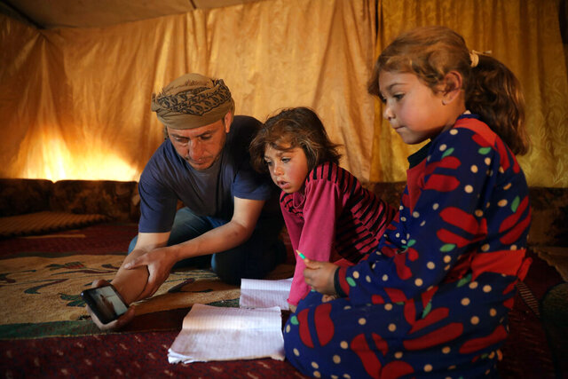 In this April 13, 2020 photo, Tariq al-Obeid, displaced from the eastern countryside of Idlib, Syria, shows a lesson for his children on a mobile phone in Kelly, a town in northern Idlib. Al-Obeid received the education material from a teacher on a private WhatsApp group. As the world moves online, the Syrians in opposition-held areas are too. In the time of coronavirus, the internet is becoming an educational tool, and one to salvage bonds essential for surviving the brutal conflict. (AP Photo/Ghaith Alsayed)