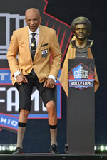 Drew Pearson, a member of the Pro Football Hall of Fame Class of 2021, shows his skinny legs during the induction ceremony at the Pro Football Hall of Fame, Sunday, Aug. 8, 2021, in Canton, Ohio. (AP Photo/David Richard)