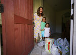 In this July 21, 2021, photo, Cynthia Carrasco White and her daughters, Charlotte, 6 and Mathilde, 3 receive a Walmart purchase delivered by Instacart at their front door home in the Porter Ranch area of Los Angeles. Carrasco White, a single mother and a lawyer for a Los Angeles nonprofit, used to think delivery was a luxury she couldn't afford. But she started getting meals, groceries and other necessities delivered last year so she could avoid taking her young, unvaccinated daughters to the store.White has come to see delivery as a lifeline that saves her time, gas money and child care expenses. She uses various apps, including Uber Eats and DoorDash, and takes advantage of deals when she can. (AP Photo/Damian Dovarganes)