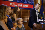 Flanked by family members, former Kansas Secretary of State Kris Kobach addresses the crowd as he announces his candidacy for the Republican nomination for the U.S. Senate Monday, July 8, 2019, in Leavenworth, Kan. (AP Photo/Charlie Riedel)