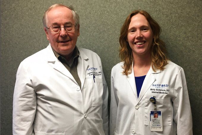 In a photo provided by Sanford Health, Dr. Jim Buhr, left, and Dr. Misty Anderson of Sanford Health in Valley City, N.D., pose for a photo Thursday, April 2, 2020. The 74-year-old Buhr is delaying his retirement in order to help the small hospital deal with possible COVID-19 cases. He said that while his age puts him at greater risk than the 38-year-old Anderson, he wants to help to protect younger workers. (Sanford Health via AP)