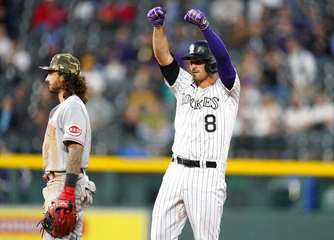 Colorado Rockies' Josh Fuentes (8) gestures toward the dugout after hitting an RBI-double off Cincinnati Reds starting pitcher Wade Miley in the fourth inning of a baseball game Friday, May 14, 2021, in Denver. (AP Photo/David Zalubowski)