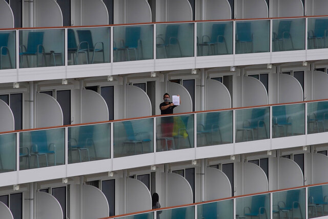 A passenger shows a note from the World Dream cruise ship docked at Kai Tak cruise terminal in Hong Kong, Wednesday, Feb. 5, 2020. A Hong Kong official says more than 3,600 people on board the cruise ship that was turned away from a Taiwanese port will be quarantined until they are checked for a new virus. (AP Photo/Vincent Yu)