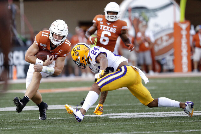 Texas quarterback Sam Ehlinger (11) runs from LSU cornerback Derek Stingley Jr. (24) during the first half of an NCAA college football game Saturday, Sept. 7, 2019, in Austin, Texas. (AP Photo/Eric Gay)