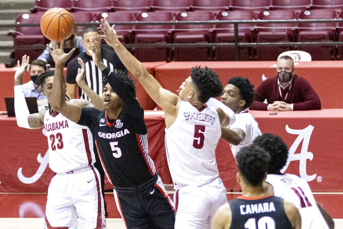 Georgia guard Justin Kier (5) passes the ball out after Alabama guards John Petty Jr. (23) and Jaden Shackelford (5) double up on him during the first half of an NCAA college basketball game on Saturday, Feb. 13, 2021, in Tuscaloosa, Ala. (AP Photo/Vasha Hunt)