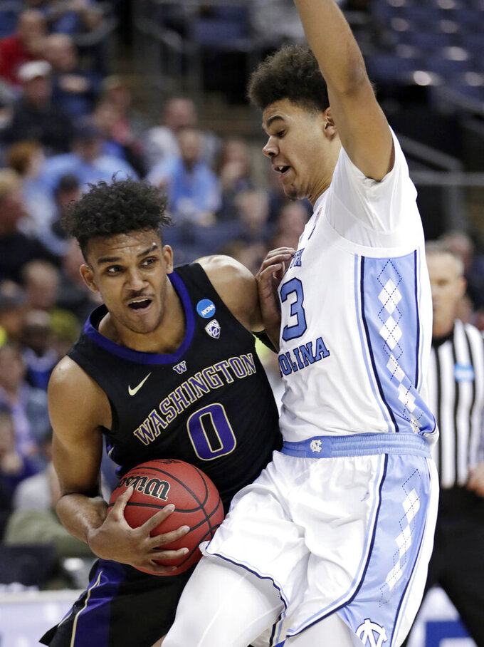 Washington's Jamal Bey (0) drives past North Carolina's Cameron Johnson (13) in the second half during a second-round men's college basketball game in the NCAA Tournament in Columbus, Ohio, Sunday, March 24, 2019. (AP Photo/Tony Dejak)