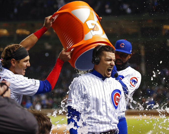 Chicago Cubs' Albert Almora Jr., left, and Jason Heyward, right, douse Javier Baez, center, with ice cubes after Baez hit a game winning RBI-single against the Philadelphia Phillies during the ninth inning of a baseball game, Tuesday, May 21, 2019, in Chicago. (AP Photo/Kamil Krzaczynski)
