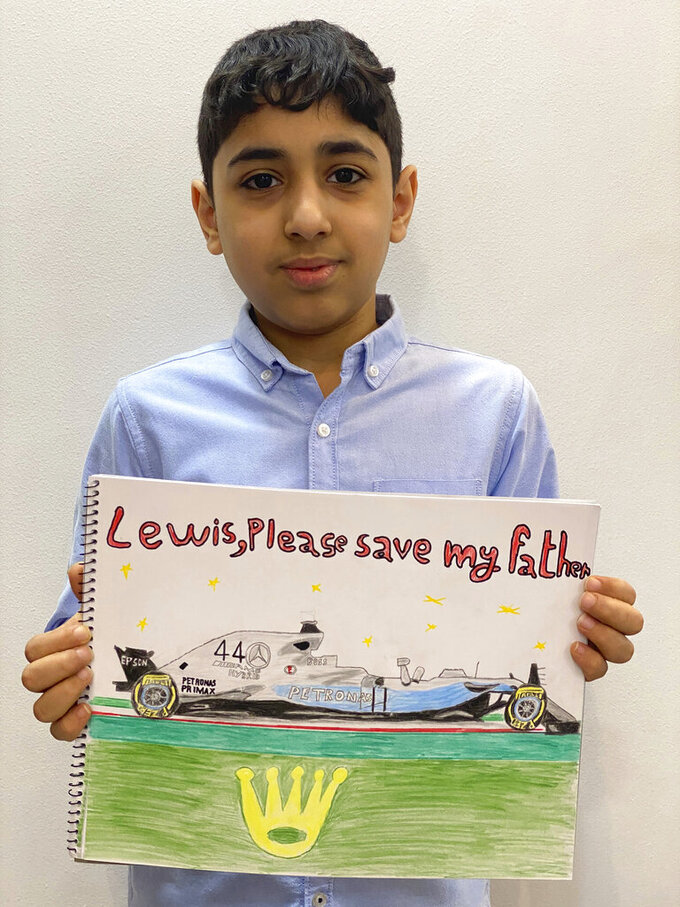 CORRECTS NAME  In this undated photo supplied by Sayed Ahmed Alwadaei, director of the London-based Bahrain Institute for Rights and Democracy (BIRD), Ahmed holds his drawing of Formula One champion Lewis Hamilton's racing car with his appeal for help in saving his father from execution. The 11-year old Ahmed is son of a Bahraini man on death row and at risk of imminent execution in Bahrain. BIRD has received letters from alleged torture victims in Bahrain, with pleas for seven-time F1 champion Hamilton to help political prisoners in Bahrain. (Photo by mother of Ahmed/BIRD via AP)