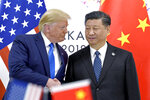 FILE - In this June 29, 2019, file photo, U.S. President Donald Trump, left, shakes hands with Chinese President Xi Jinping during a meeting on the sidelines of the G-20 summit in Osaka, western Japan. The director of US intelligence on Friday raised concerns about interference in the 2020 election by China, Russia and Iran.  U.S. intelligence has assessed that China is hoping President Donald Trump does not win reelection, Russia is working to denigrate Democrat Joe Biden and Iran is seeking to undermine democratic institutions, said the director of counterintelligence, Bill Evanina.(AP Photo/Susan Walsh, File)