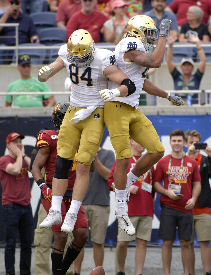 Notre Dame wide receiver Chase Claypool, right, is congratulated by tight end Cole Kmet (84) after catching a 24-yard touchdown pass during the first half of the Camping World Bowl NCAA college football game Saturday, Dec. 28, 2019, in Orlando, Fla. (AP Photo/Phelan M. Ebenhack)